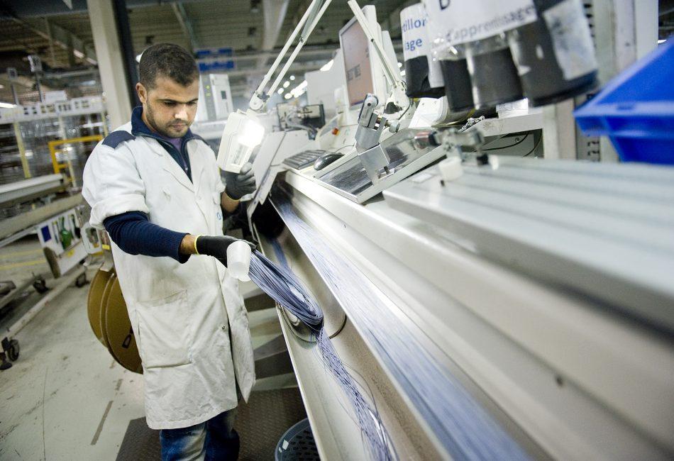 Marokko werk taan de uitbreiding van haar auto-industrie. In de haven van tanger staan honderden auto's te wachten om naar Europa verscheept te worden. Bij SEBN in de Tanger Free Zone worden de elektrische kabels voor in auto's bij elkaar gebonden met tape.